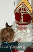 Saint NIcolas visits a home, and checks his book for children's behavior