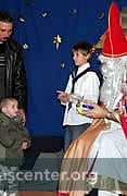 Angel helpers assist St. Nicholas as he gives treats to the children