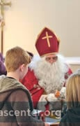 St Nicholas receives toys from the children to be given to those in need