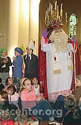 Children surround the good saint during the service