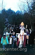 Children and families meet Samichlaus in the forest and come down to the town
