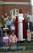 St Nicholas with children holding donated toys