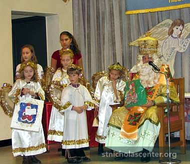 St. Nicholas, attended by angel helpers, talks to everyone