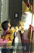 St Nicholas and his Deacon and Chaplain have teddybears for children; oranges,  chocolate coins, and prayer cards for everyone