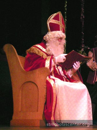 Sinterklaas reads from his big book about the good deeds children have done