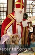 Sinterklaas talks with children at the party