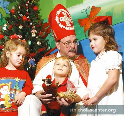 Pastor Mitchell Williams, as St. NIcholas, meets with children at the church's preschool