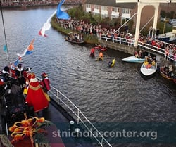 Sinterklaas boat on canal, lined by crowds