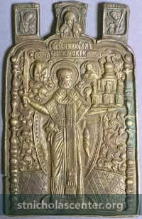 In Russia St. Nicholas the Wonderworker is often shown as Holy Hierarch Nicholas of Mozhaisk. These icons show a full-length Nicholas with a sword in his right hand and a city in his left because the prayers of St. Nicholas saved the city of Mozhaisk from enemy attack. 18th Century Russian icon with the angels Gabriel and Michael at the top with the Vernicle (Holy Face). —St. Nicholas Center Collection