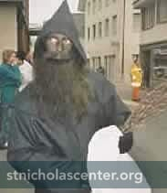 Hooded black-robed figure with dark beard
